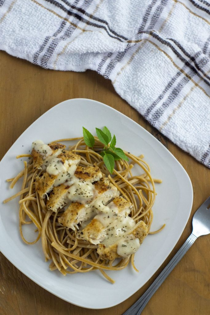 White Cheddar Chicken Pasta garnished with a sprig of basil on a square white plate next to a stainless steel fork with a white and brown towel behind all on a wooden surface (vertical)