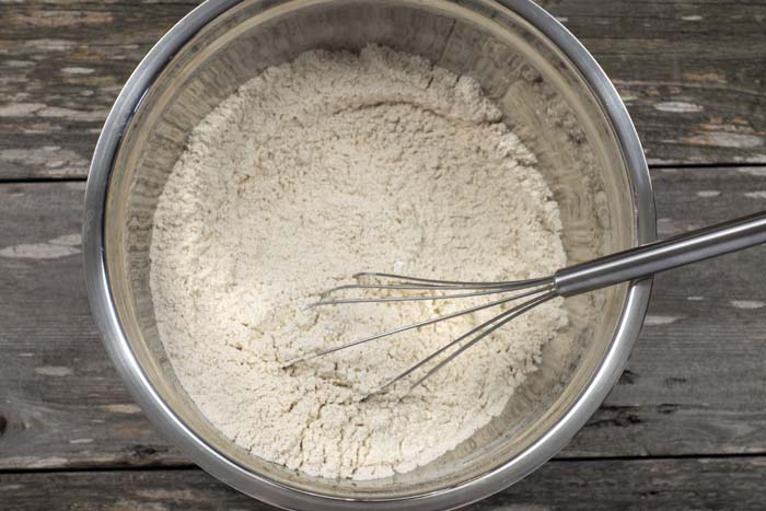 Combined dry ingredients with a wire whisk in a stainless steel bowl on a wooden surface
