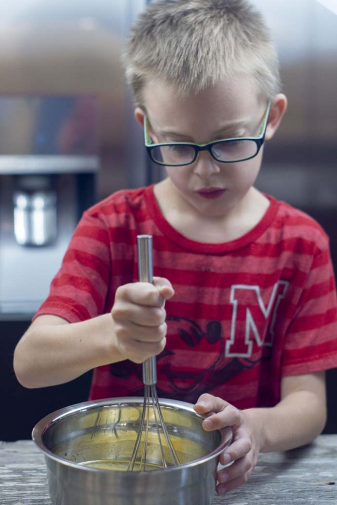 Young boy using a wire whisk to stir wet ingredients in a stainless steel bowl on a wooden surface