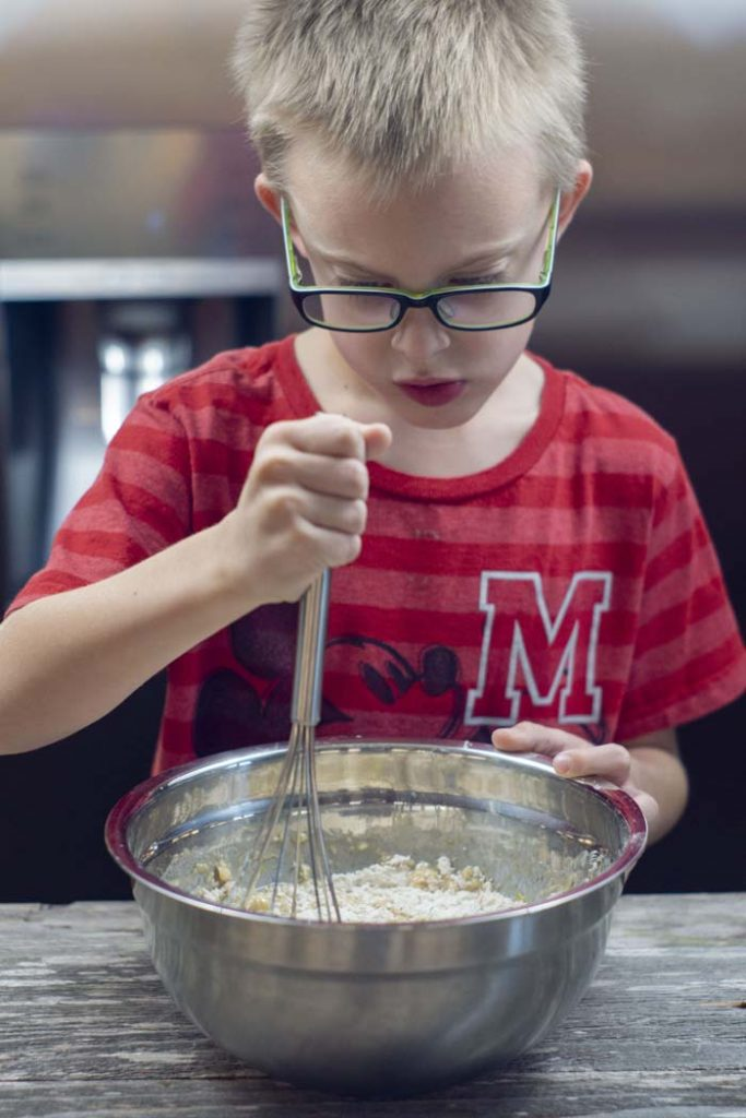 Young boy whisking muffin batter in a stainless steel bowl on a wooden surface