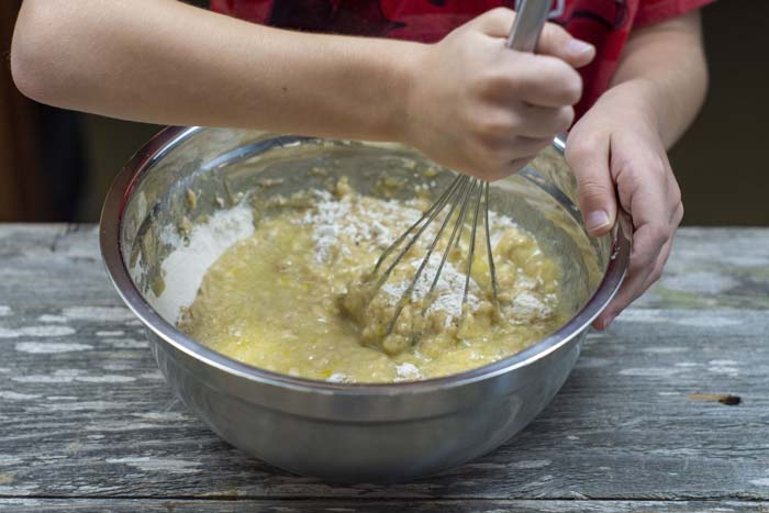 Young boys hands using a wire whisk to stir muffin batter in a stainless steel bowl on a wooden surface
