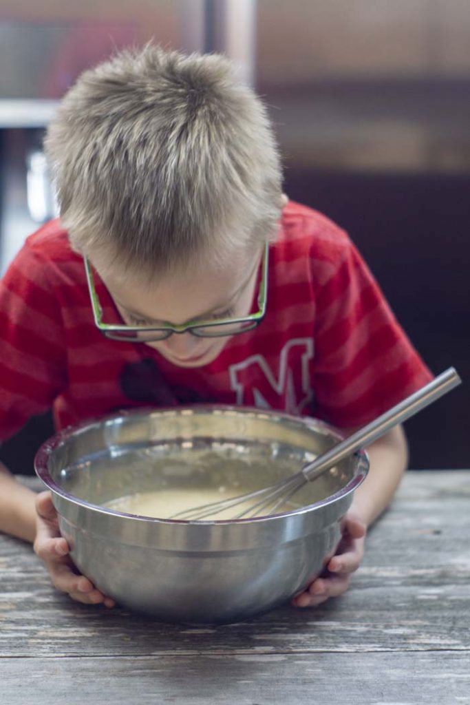 Young boy sniffing over a stainless steel bowl with a wire whisk on a wooden surface