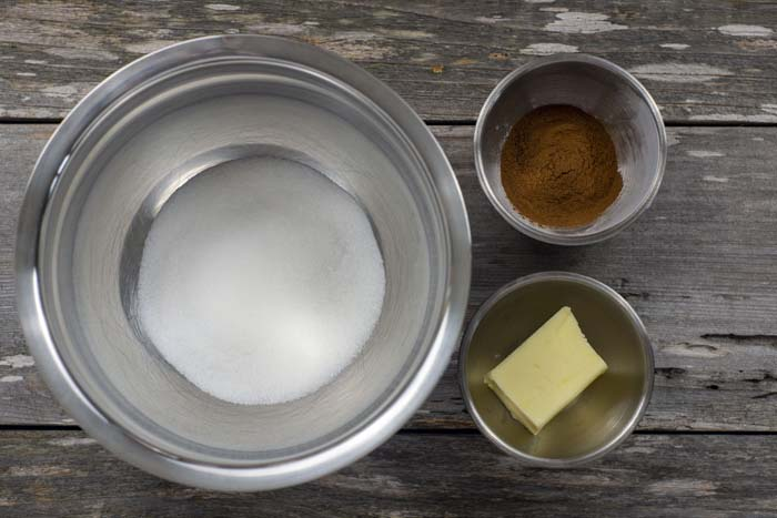 Stainless steel bowls with sugar, cinnamon, and butter on a wooden surface