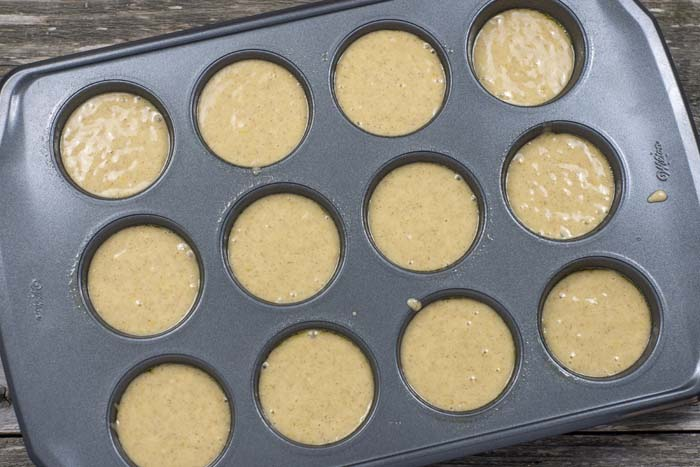 Muffin batter filling a 12-cup metal muffin pan on a wooden surface