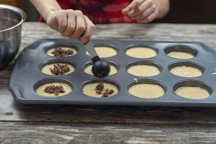 Young boy using a measuring spoon to add streusel to the muffin batter in a metal muffin pan on a wooden surface