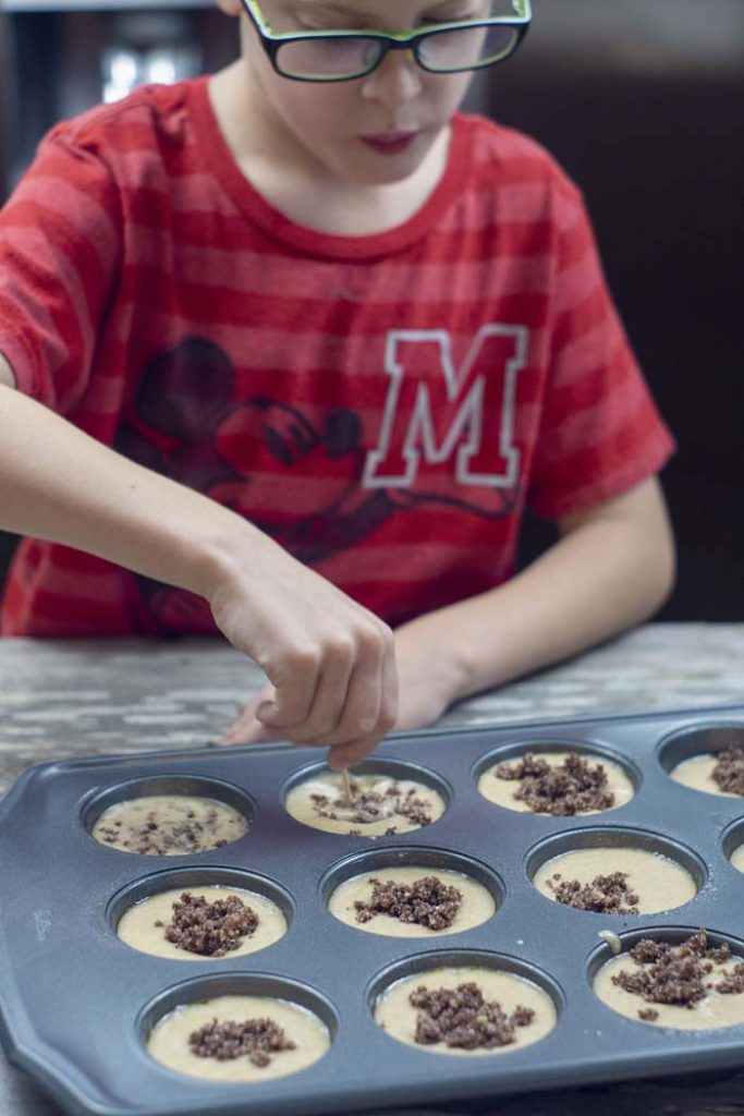 Young boy using a toothpick to swirl cinnamon streusel into muffin batter in a metal muffin pan