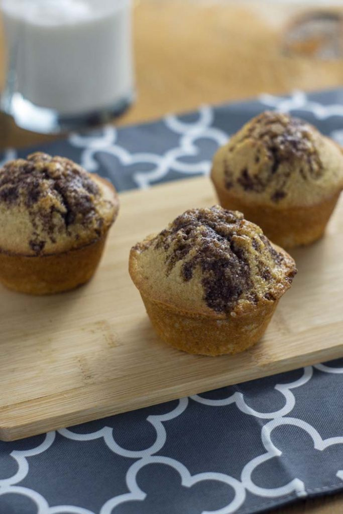 3 Cinnamon Swirl Muffins with Streusel Topping on a bamboo board on top of a grey and white placemat with a glass of milk behind all on a wooden surface (vertical)