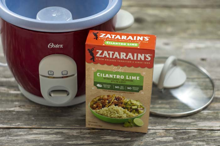 Empty rice steamer next to the lid with a box of Zatarain's rice in front all on a wooden surface