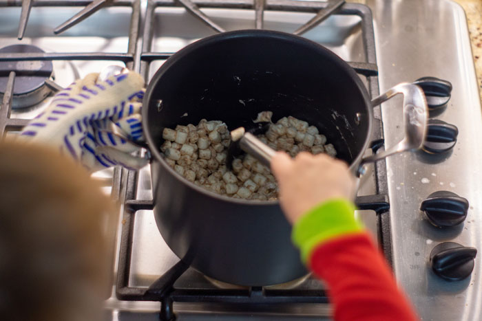 Over-the-shoulder view of a young boy using a metal spoon to stir marshmallows covered with melted butter and cinnamon in a large stockpot over a gas stovetop