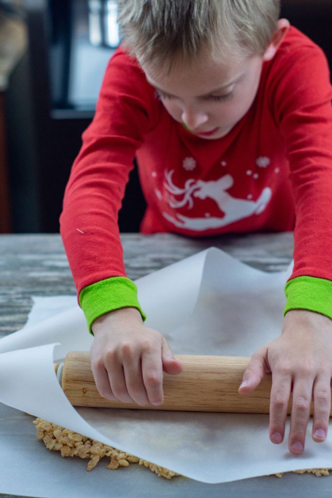 Young boy using a wooden rolling pin to flatten rice Krispies between two pieces of parchment paper on a wooden surface