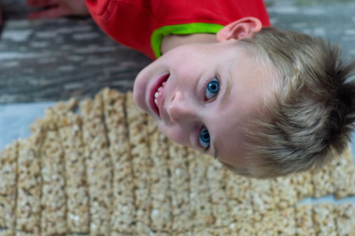 Young boy looking up into the overhead camera above churro rice krispies on a piece of parchment paper on a wooden surface