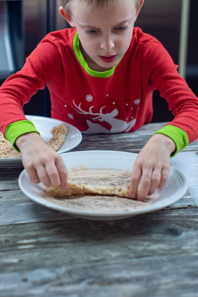 Young boy rolling a strip of churro rice krispies in cinnamon-sugar on a round white plate with another round white plate of churro rice krispies behind and a piece of wax paper to the right all on a wooden surface