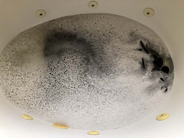 Oven grates and racks in a large bathtub with soapy water