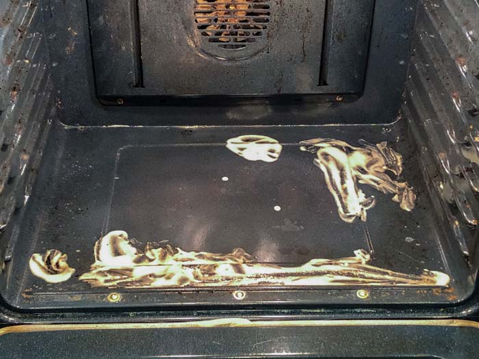 Dirty oven with baking soda paste on the dirty areas