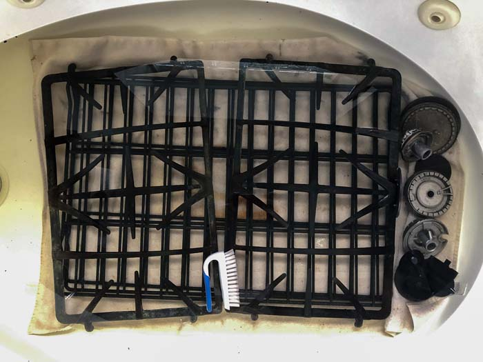 Oven racks and grates in a large bathtub covered with water with a scrubbing brush