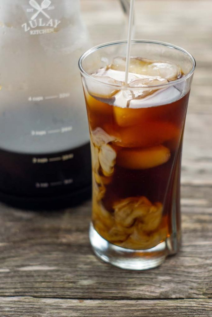 Cold brew coffee with cubes of ice in a glass cup with a carafe of cold brew coffee behind on a wooden surface (vertical)