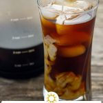 Cold brew coffee with cubes of ice in a glass cup with a carafe of cold brew coffee behind on a wooden surface (vertical with title overlay and short description)