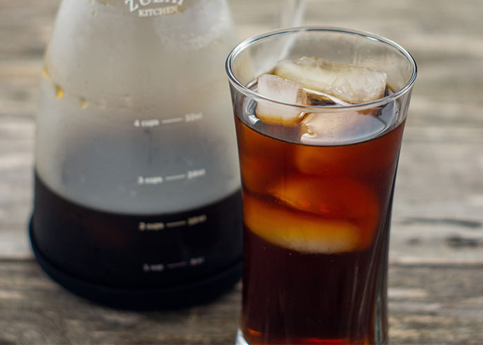 Cold brew coffee with cubes of ice in a glass cup with a carafe of cold brew coffee behind on a wooden surface