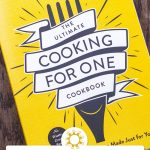Front cover of The Ultimate Cooking For One Cookbook on a wooden surface with title overlay