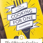 Front cover of The Ultimate Cooking For One Cookbook on a wooden surface with large title overlay in a white box