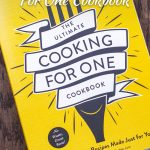Front cover of The Ultimate Cooking For One Cookbook on a wooden surface with large title overlay