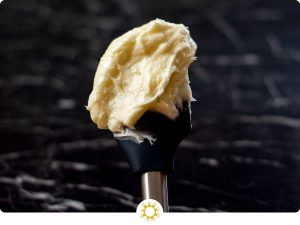 Large scoop of cream cheese frosting on a black rubber spatula with a metal handle over a black and white marble surface (with logo overlay)