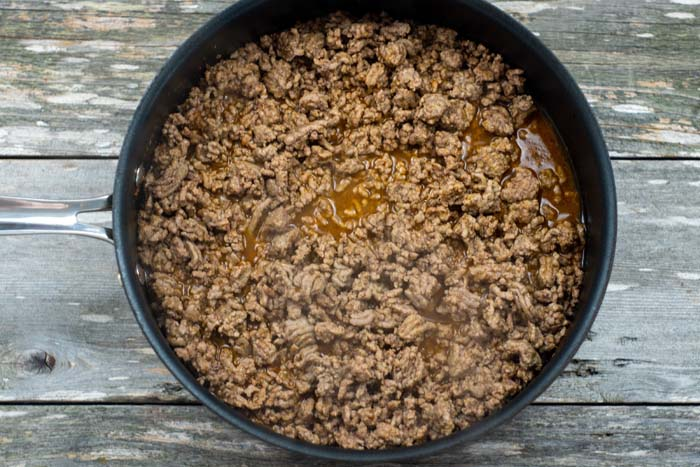 Browned ground beef with water and taco seasoning in a nonstick skillet on a wooden surface
