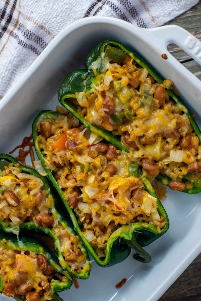 Cooked taco-stuffed poblano peppers in a white casserole dish with a white and brown towel behind all on a wooden surface (vertical)