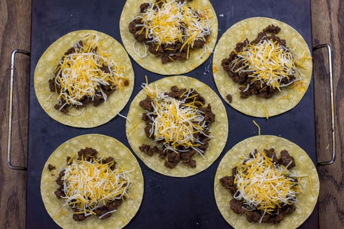 6 corn tortillas topped with a scoop of prepared taco meat and shredded cheese on a baking stone on a wooden surface