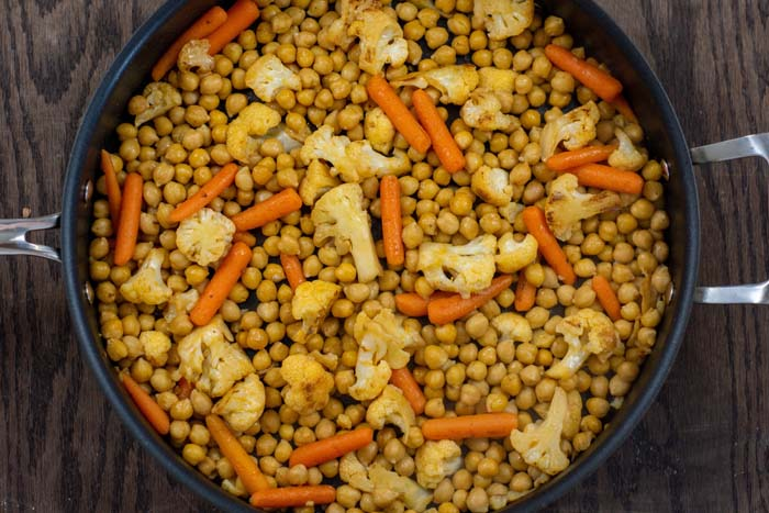 Chopped cauliflower, baby carrots, and chickpeas in a large nonstick skillet on a wooden surface