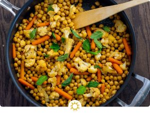 Chopped cauliflower, baby carrots, and chickpeas topped with mint leaves with a wooden spoon in a large nonstick skillet on a wooden surface (with logo overlay)