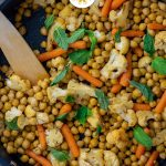Chopped cauliflower, baby carrots, and chickpeas topped with mint leaves with a wooden spoon in a large nonstick skillet on a wooden surface (vertical with title overlay)