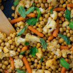 Chopped cauliflower, baby carrots, and chickpeas topped with mint leaves with a wooden spoon in a large nonstick skillet on a wooden surface (vertical with simple title overlay)