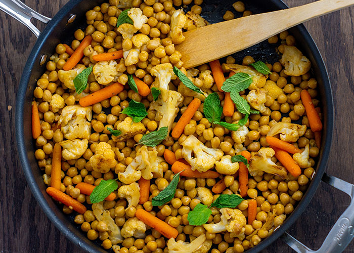 Chopped cauliflower, baby carrots, and chickpeas topped with mint leaves with a wooden spoon in a large nonstick skillet on a wooden surface