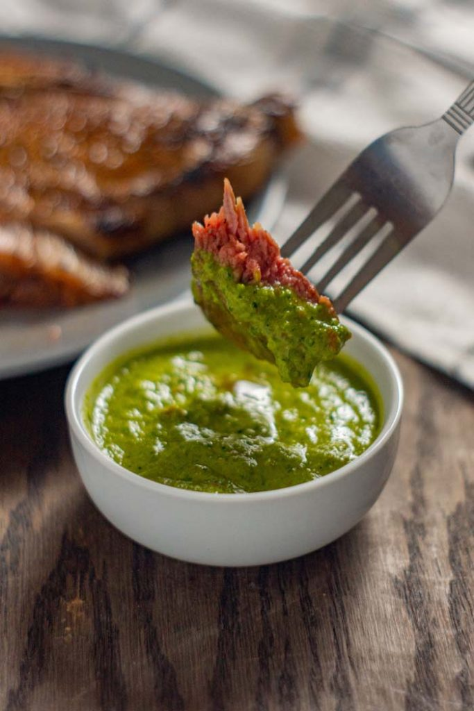 Piece of cooked steak on a stainless steel fork being dipped into a round white bowl of green chimichurri sauce with a plate of grilled steak in the back next to a white and grey towel all on a wooden surface