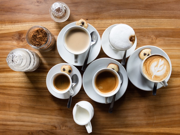 Overhead view of coffee and lattes in mugs on saucers all on a wooden surface