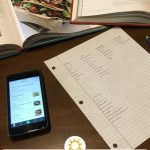 Two cookbooks, a cell phone, a piece of paper with a grocery list, and an LED tablet all on a wooden surface (with title overlay)