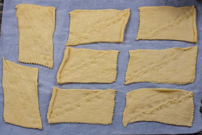 Flattened crescent rolls on parchment paper