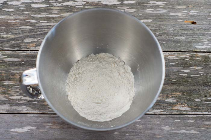 Dry ingredients in a stainless steel mixing bowl on a wooden surface