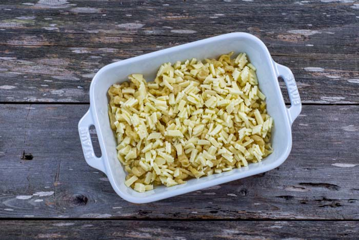 Single layer of spaetzle noodles topped with cheese in a white casserole on a wooden surface