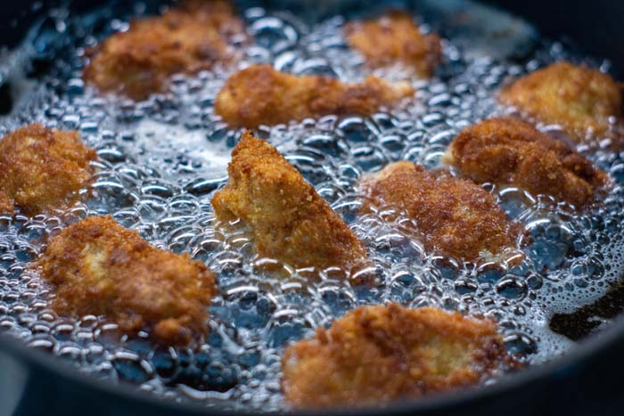 Breaded chicken pieces frying in oil in a skillet