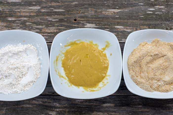 Three white bowls with flour in one, egg and dijon mustard in another, and bread crumbs in the last all on a wooden surface