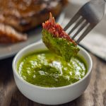 Piece of cooked steak on a stainless steel fork being dipped into a round white bowl of green chimichurri sauce with a plate of grilled steak in the back next to a white and grey towel all on a wooden surface (with title overlay)