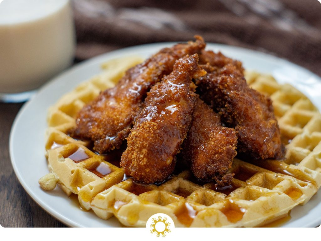Fried chicken on top of a waffle covered with syrup on a round white plate with a glass of milk and a brown and white towel behind the plate all on a wooden surface (with logo overlay)