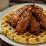 Fried chicken on top of a waffle covered with syrup on a round white plate with a glass of milk and a brown and white towel behind the plate all on a wooden surface (with simple title overlay)