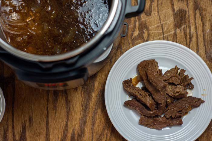 Cooked beef strips on a round white plate next to an instant pot with sauce on a wooden surface