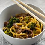 Beef and broccoli with udon noodles in a round white bowl with wooden chopsticks on a grey placemat all on a white surface (with title overlay)