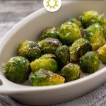 Garlic-Parmesan Brussels Sprouts in a white oval dish on top of a grey napkin on a wooden surface (with title overlay)