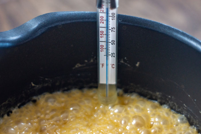 Close up of a candy thermometer in a saucepan full of bubbling fudge ingredients