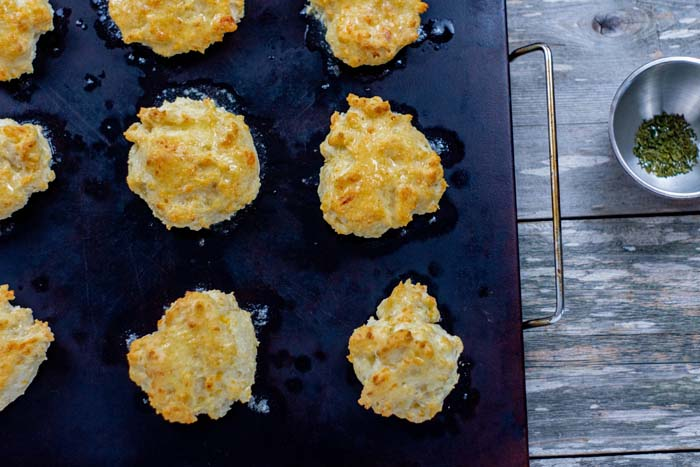 Baked cheddar biscuits brushed with melted butter on a baking stone next to a stainless steel bowl of crushed parsley all on a wooden surface